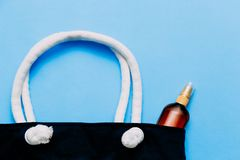 Striped beach bag and suntan oil on blue background. The concept of a beach holiday. Striped beach bag and suntan oil on blue background royalty free stock image
