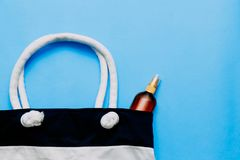 Striped beach bag and suntan oil on blue background. The concept of a beach holiday. Striped beach bag and suntan oil on blue background stock images
