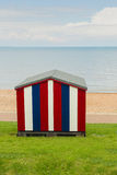 Striped beach hut on grass, by the sea Stock Photo