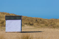 Striped beach hut on sandy beach. Secluded beach vacation. Stock Photo