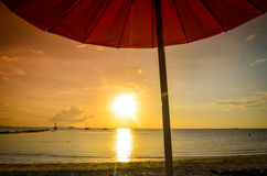 Striped beachchairs and sunshade at sunset Royalty Free Stock Images