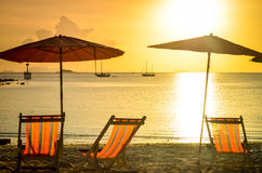 Striped beachchairs and sunshade at sunset Stock Images