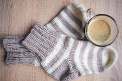 Striped beige-white knitted socks and the black coffee Royalty Free Stock Photos