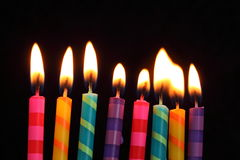 Striped birthday candles. Lit multi colored birthday candles with flames Stock Photos