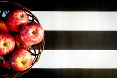 Striped black and white background. Red apples on striped black and white background. Flat lay, top view, space for text royalty free stock photo