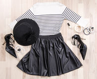 Striped blouse and leather skirt with accessories arranged on the floor. Stock Images