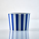 Striped blue and white disposable food container. Striped blue and white disposable cardboard food container or tub for serving takeaway refreshments on a Royalty Free Stock Photos