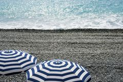 Striped blue and white umbrellas on a pebble beach on the Promenade des Anglais in Nice, France, await guests. Blue waves roll stock photo