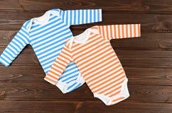 2 striped bodysuits младенца на деревянной предпосылке Стоковые Изображения RF