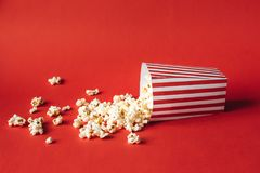 Striped box with popcorn. On red background Stock Image