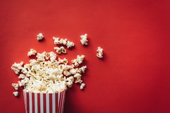 Striped box with popcorn. On red background Royalty Free Stock Photos