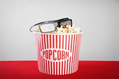 Striped bucket with tasty popcorn and glasses stock image