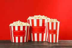 Striped buckets with popcorn against red background