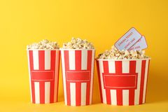 Striped buckets with popcorn on yellow background