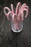 Striped candy canes in faceted glass on wood table Royalty Free Stock Images