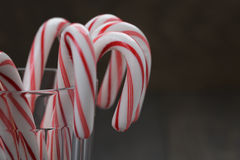 Striped candy canes in faceted glass on wood table Stock Photo