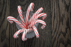 Striped candy canes in faceted glass on wood table Royalty Free Stock Photography