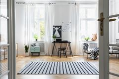 Black chair at desk in child`s room interior with windows, bed and plants. Real photo. Striped carpet near black chair at desk in child`s room interior with stock photo