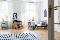Striped carpet and windows in white teenager`s room with black chair at desk near bed royalty free stock image
