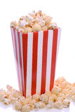 Striped carton of popcorn. Overflowing red and white striped carton of fresh popcorn with studio background stock photos