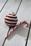 Striped christmas bauble and candy cane on wooden background Stock Images