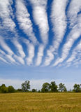 Striped clouds over the cleaned wheaten field Stock Image