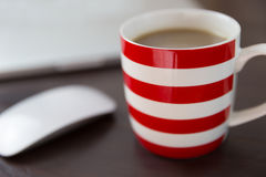 Striped coffee mug and computer on office desk. Taking a break at work Stock Images