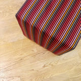 Striped cube chair on wooden floor Royalty Free Stock Photos