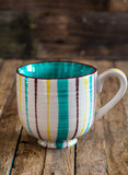 The striped Cup on wooden background Royalty Free Stock Photography