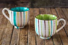 The striped Cup on wooden background Stock Images