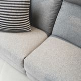 Striped cushion decorating a gray textile sofa. Comfortable furniture royalty free stock photography