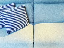 Striped cushions on a blue textile sofa Royalty Free Stock Image