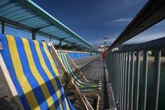 Striped Deckchair on seaside  Pier. Striped deck chairs on Seaside pier, Bournemouth, England Stock Photos