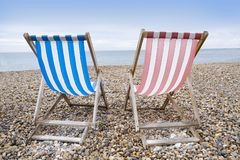 Striped deckchairs on pebble beach stock photos