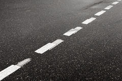 Striped dividing marking line on aspahalt road Royalty Free Stock Photography