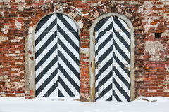 Striped doors on brick facade. Two striped doors on a brick facade of the old fort Royalty Free Stock Image