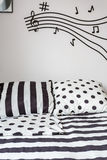 Striped and dotted sheet on bed Royalty Free Stock Images