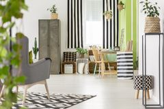 Striped drapes in modern apartment interior with metal cabinet a. Nd grey armchair on carpet. Real photo stock photos