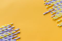 Striped drink straws of different colors in row isolated on yellow background. Minimalism concept. Pop art style. Flat. Striped drink straws of different colors stock photography