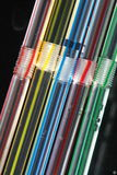 Striped Drinking Straws. Closeup abstract view of five striped drinking straws arranged in a row vertically at a slight angle, isolated against a black Stock Photography