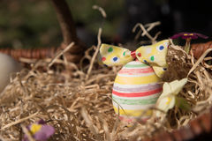 Striped easter egg in a basket Royalty Free Stock Photography