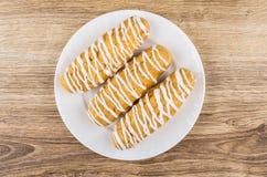 3 striped eclairs в белой плите на деревянном столе Стоковая Фотография