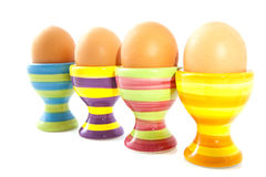 Striped eggcups. Four colorful striped eggcups in a row  over white Royalty Free Stock Photography