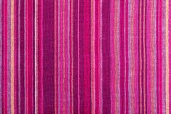 Striped fabric texture with multiple warm colors purple, purple, magenta, pink, red, maroon, orange, yellow. royalty free stock photography