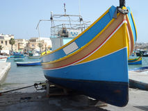 Striped Fishing Boat in Marsaxlokk Harbour. Traditional brightly coloured wooden fishing boat on the harbourside at Marsaxlokk fishing village Stock Photo