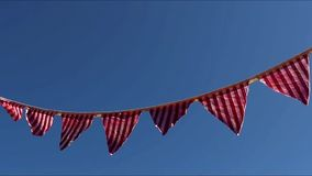Striped flag banner on a clear blue skyblowing in the breeze stock video footage