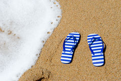 Striped flip flops at the beach. Pair of striped flip flops at the beach Royalty Free Stock Photo