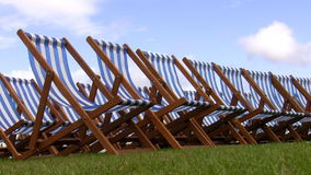 Striped folding chairs on the grass stock footage