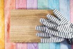 Striped gardening gloves on a wood plank, over a pastel wooden rainbow background. Useful for spring gardening concepts and. Projects royalty free stock photos