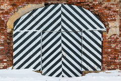 Striped gate on brick facade Royalty Free Stock Photography